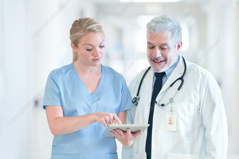 Mature doctor with colleague using tablet
