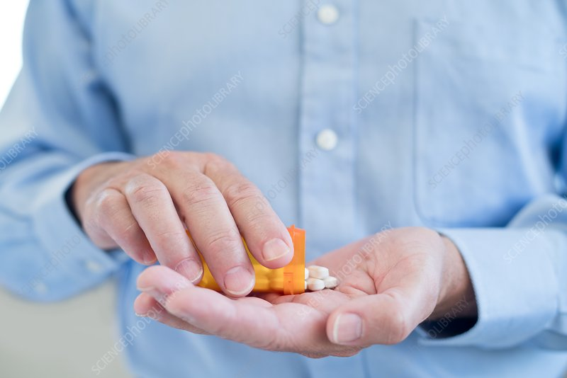 Man pouring pills onto hand from bottle