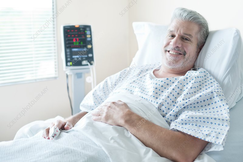 Mature male patient in hospital bed, smiling