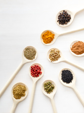 Dried spices on white spoons
