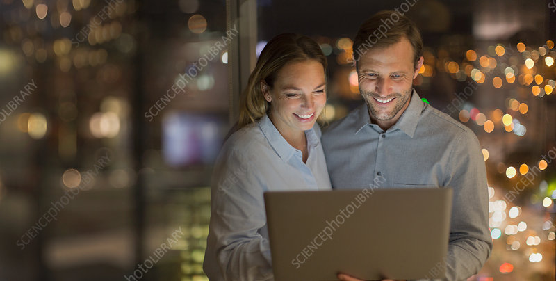 Smiling businessmen working late at laptop