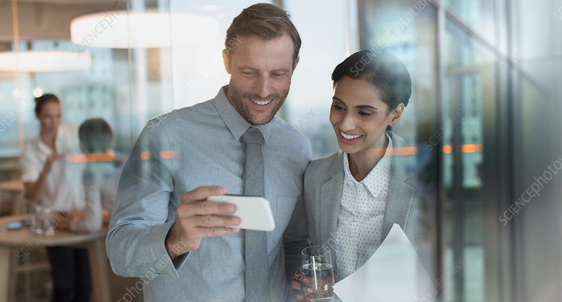 Smiling businessmen watching video on smart phone