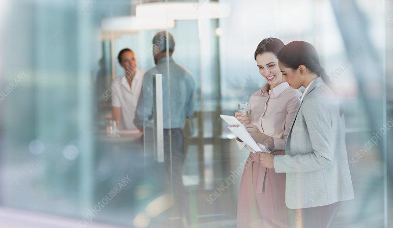 Businesswomen talking, reviewing paperwork
