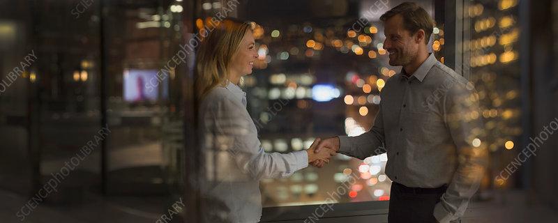 Businessman and businesswoman handshaking
