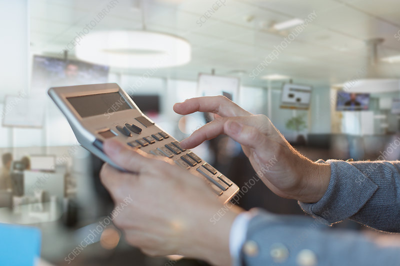 Close up businessman using large calculator