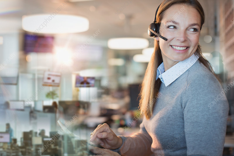 Smiling businesswoman with headset working