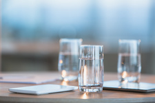 Water in glasses next to digital tablets on table