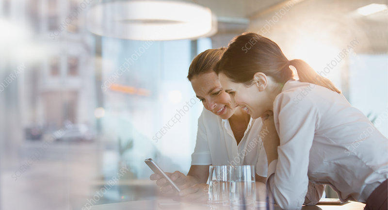 Businesswomen texting with cell phone