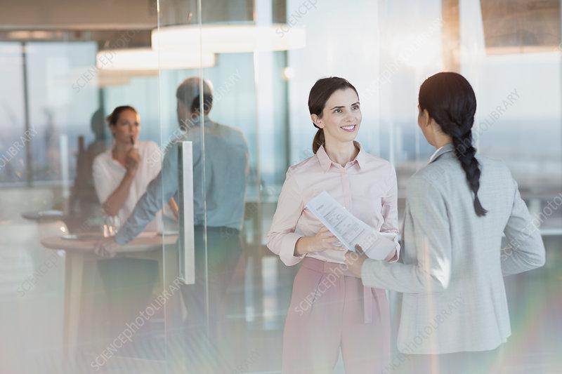 Businesswomen with paperwork talking