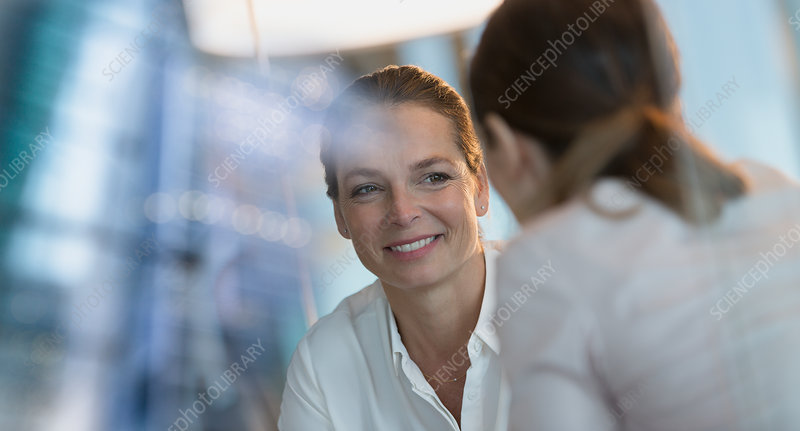 Smiling businesswoman listening to colleague