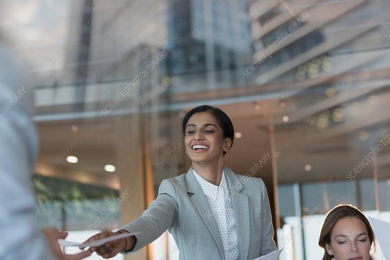 Businesswoman handing paperwork to colleague