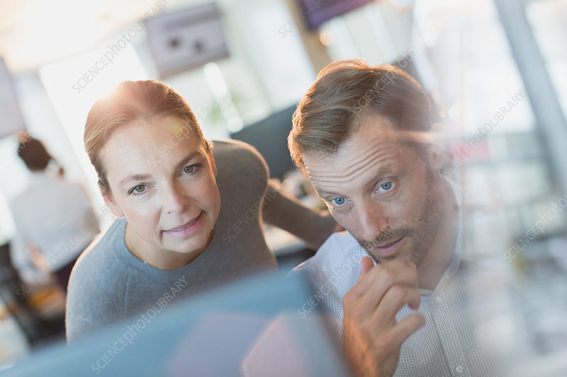 Businessman and businesswoman working at computer