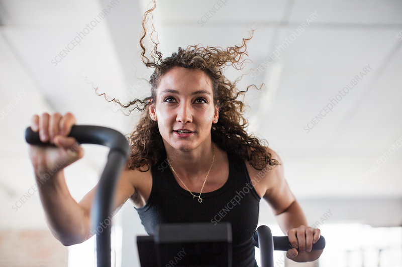 Determined woman using elliptical trainer