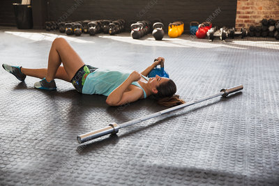 Young woman resting, laying on gym floor
