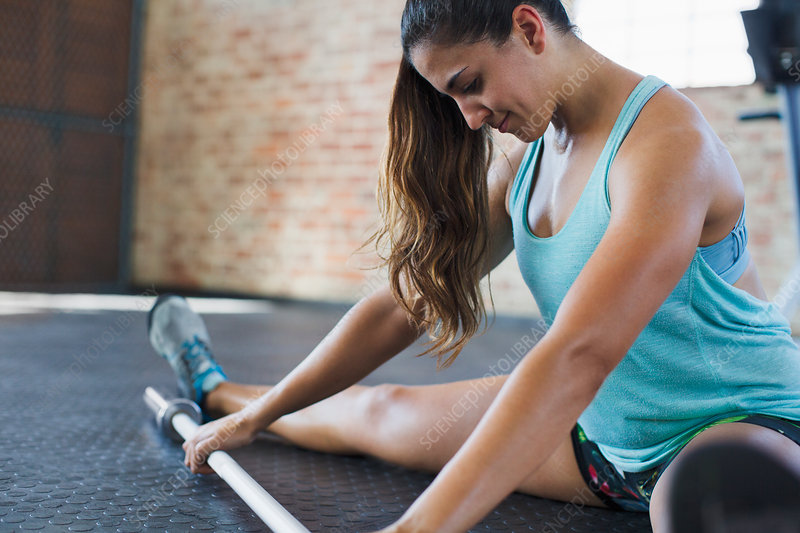Focused woman stretching leg, using barbell