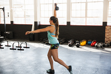 Young woman practicing lunges with kettlebell