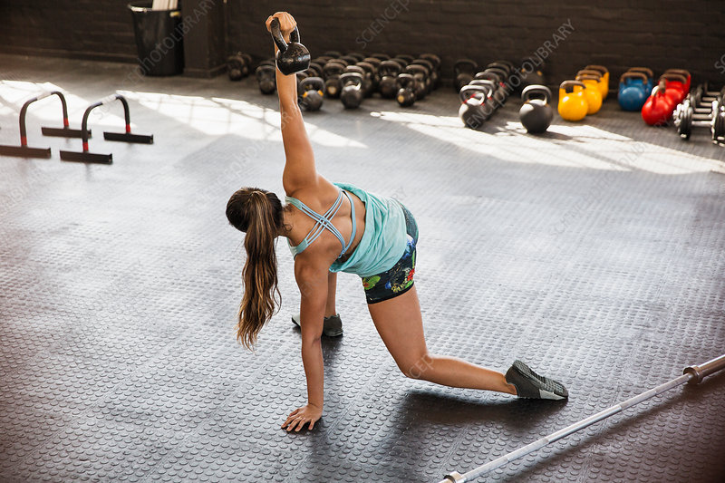 Young woman stretching, using kettle bell