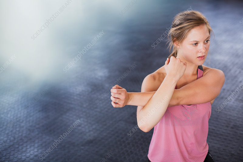 Young woman stretching arm and shoulder