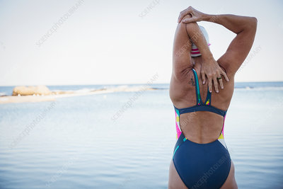 Female swimmer stretching arm and shoulder