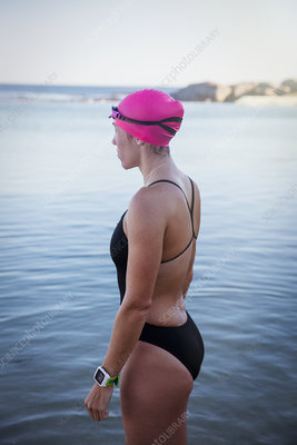 Pensive female swimmer with smart watch wading