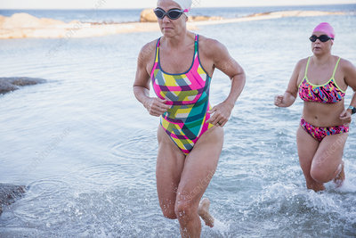 Determined female swimmers running