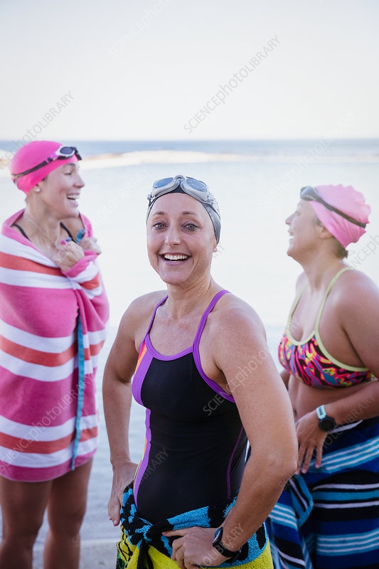 Female swimmers drying off with towels at ocean