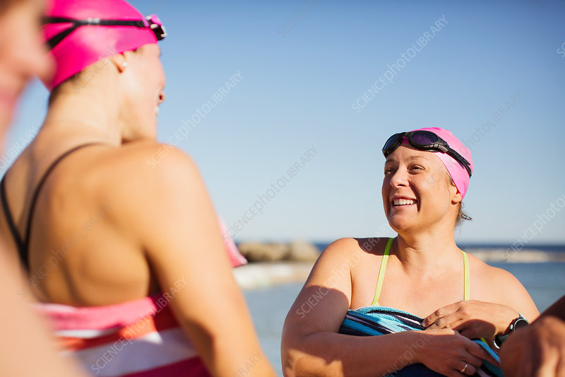 Smiling female swimmers drying off with towels