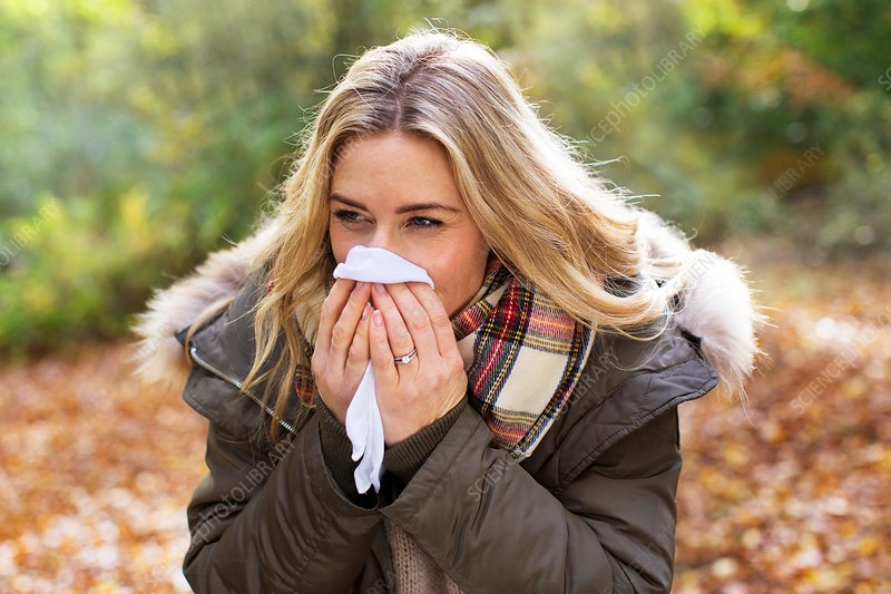 Woman blowing her nose on a tissue