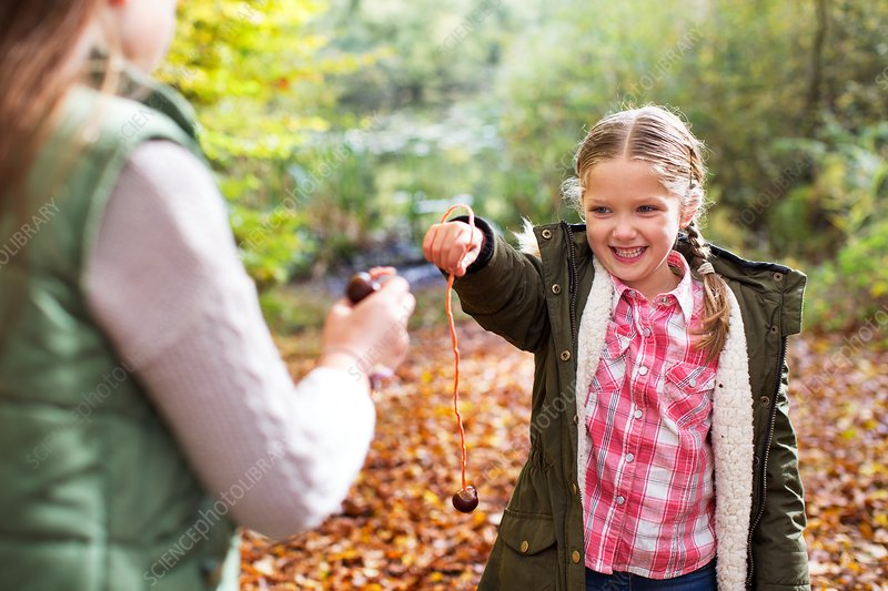 Two girls playing conkers