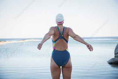 Female swimmer stretching at ocean