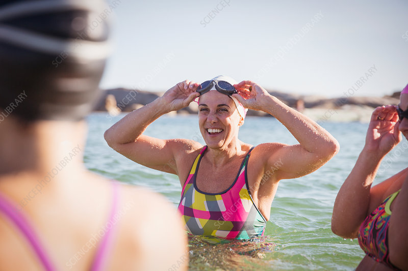 Smiling female swimmers wading