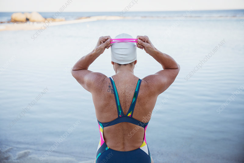 Female swimmer adjusting swimming goggles at ocean