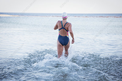 Female swimmer running into ocean surf