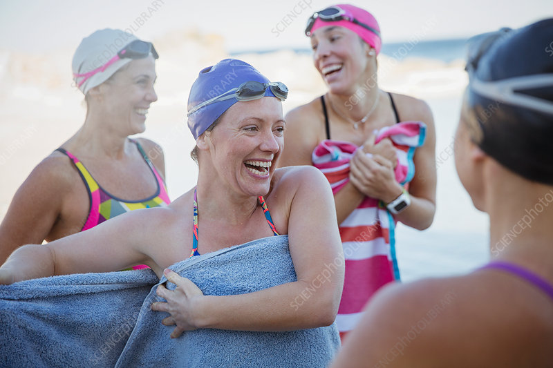 Laughing female swimmers drying off with towels