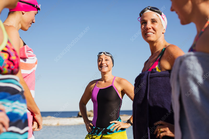Smiling female swimmers wrapped in towels