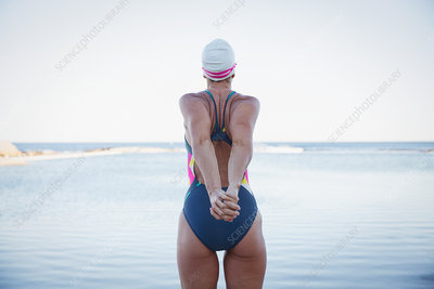 Female swimmer stretching arms at ocean
