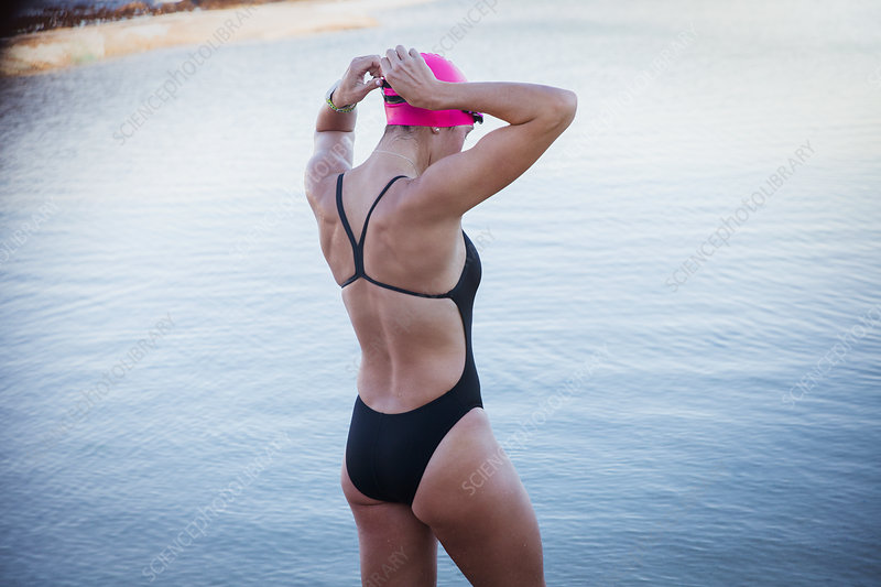 Female swimmer adjusting swimming goggles at ocean