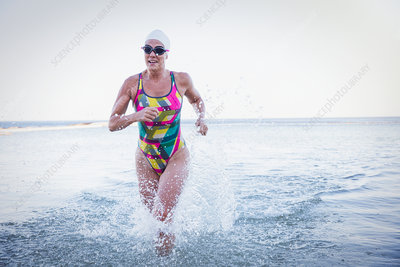 Female swimmer running and splashing
