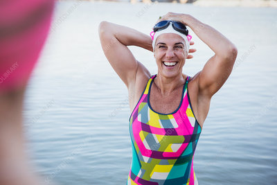 Female swimmer adjusting swimming cap in ocean