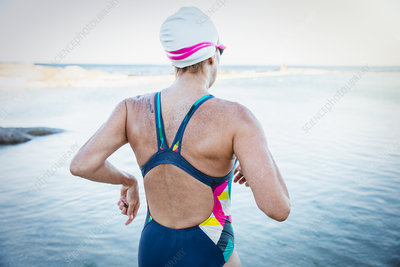 Female swimmer running into ocean