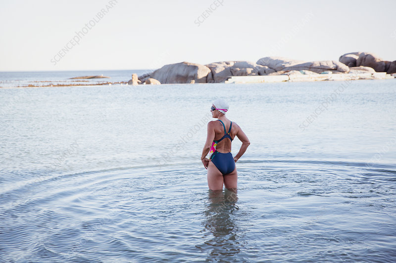 Female swimmer standing, wading in ocean