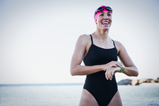 Smiling female swimmer adjusting smart watch