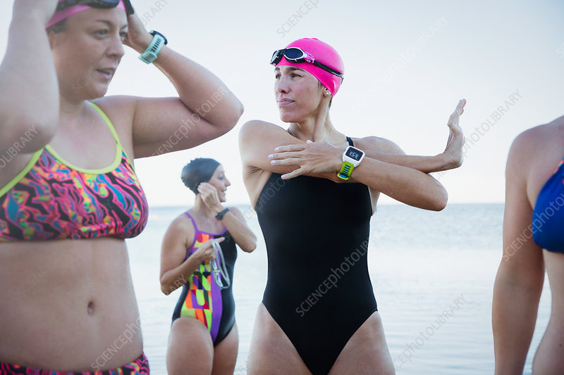 Female swimmers with smart watch stretching