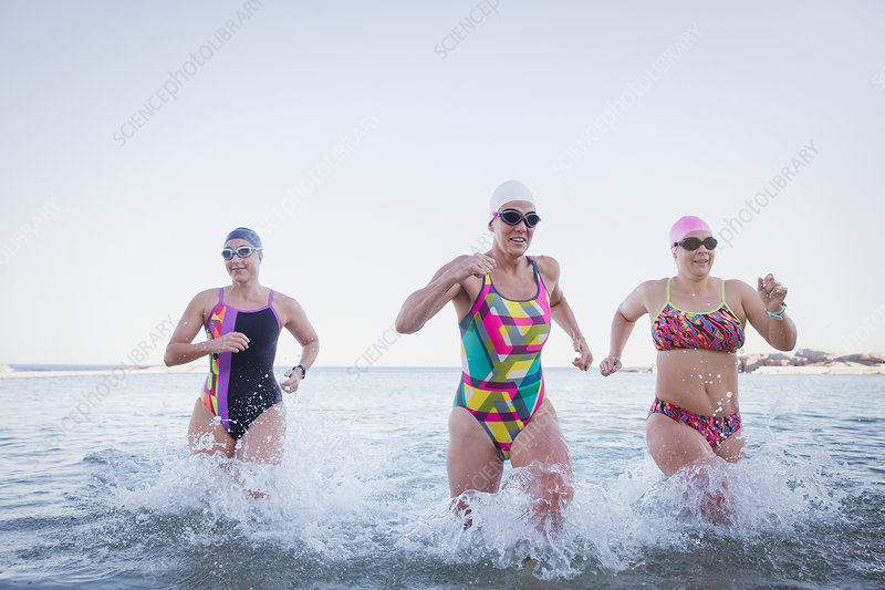 Female swimmers running and splashing