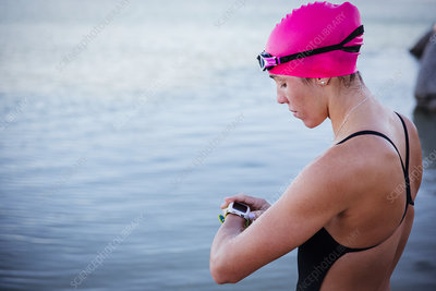 Female swimmer checking smart watch at ocean