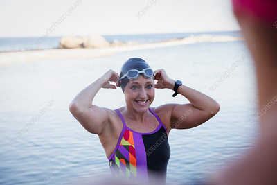 Smiling swimmer adjusting swimming cap