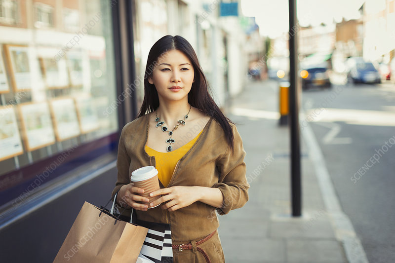 Young woman walking along storefront