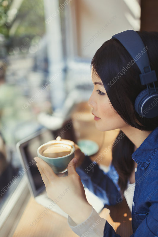 Pensive woman drinking coffee, listening to music