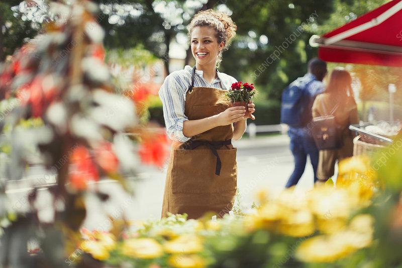 Smiling florist working at flower shop storefront