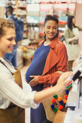 Cashier helping pregnant female shopper